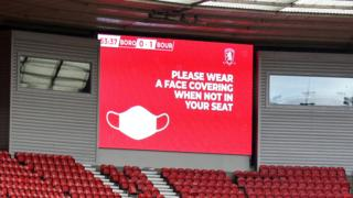 """A sign reading """"please wear a face covering when not in your seat"""" at Middlesbrough's Riverside Stadium during their Championship match against Bournemouth that saw 1,000 fans attend"""