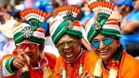 Three India cricket fans in colourful clothing