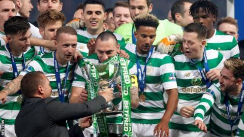 Celtic manager Brendan Rodgers hands the League Cup to captain Scott Brown