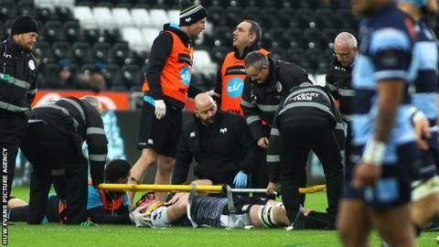 Adam Beard in a stretcher