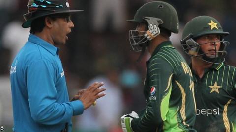 Umpire Ruchira Palliyaguruge talks to Pakistan's batsman after the ODI with Zimbabwe was halted because of bad light