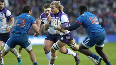 David Denton runs with the ball for Scotland as France duo Remi Lamerat and Cedate Gomes Sa try to tackle him