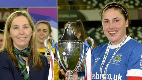 Linfield captain Sarah Venney receives the cup from Elaine Junk after goals by Kirsty McGuinness and Abbie Magee gave the Blues a 2-1 win over Cliftonville