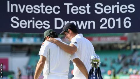 Alastair Cook and Misbah-ul-Haq embrace under an Investec banner