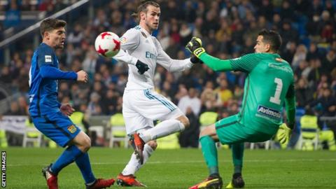 Gareth Bale of Real Madrid takes on a Fuenlabrada defender and goalkeeper in the Copa del Rey