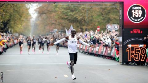 Eliud Kipchoge celebrating while crossing the finishing line after running a marathon in under two hours