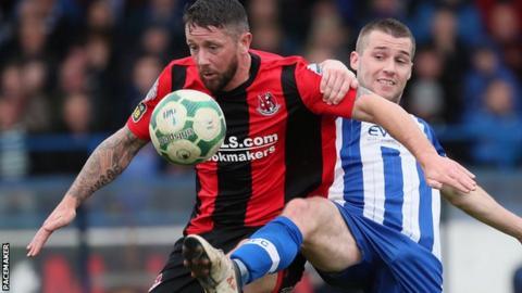 Crues striker Rory Patterson is challenged by Coleraine midfielder Stephen Lowry