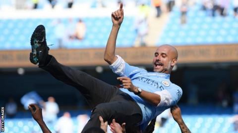 Pep Guardiola is thrown in the air in celebration by his Manchester City players