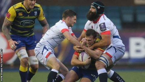 Garyn Smith of Cardiff Blues is held by Josh Strauss of Sale Sharks and Will Cliff of Sale Sharks
