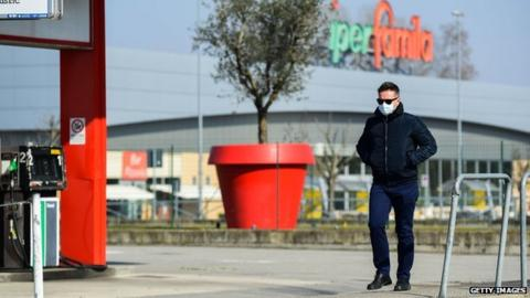 A man wearing a surgical mask walks along a deserted street in the Italian town of Codogno