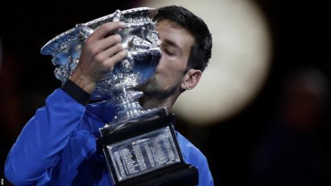 Novak Djokovic kisses the Australian Open trophy after winning the tournament in 2019