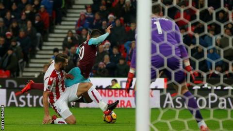 West Ham forward Manuel Lanzini falls over as he is tackled by Stoke defender Erik Pieters