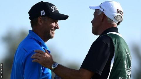 Anders Hansen shakes hands with his caddy after a third round 62