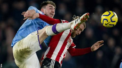 Manchester City defender Aymeric Laporte tussles with Sheffield United's Oliver McBurnie