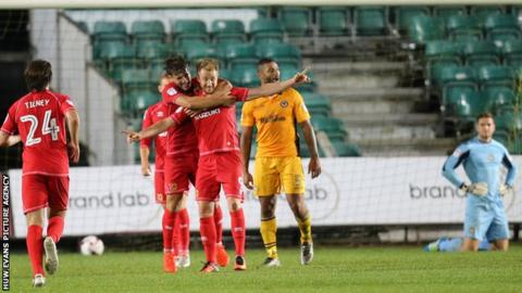 Dean Bowditch of MK Dons celebrates with team mates after he scores the winner in added time
