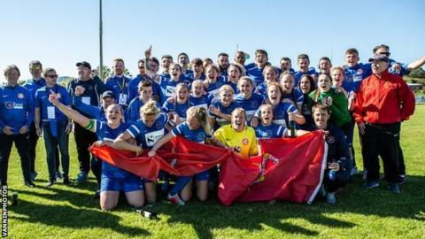 The Isle of Man women's football team celebrate their gold medal with the rest of the team