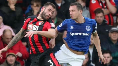 Phil Jagielka (right) challenges for a header