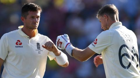 England batsmen Joe Denly (left) and Joe Root (right) bump fists during a drinks break