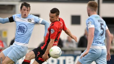 Warrenpoint skipper Danny Wallace in action against Paul Heatley of Crusaders