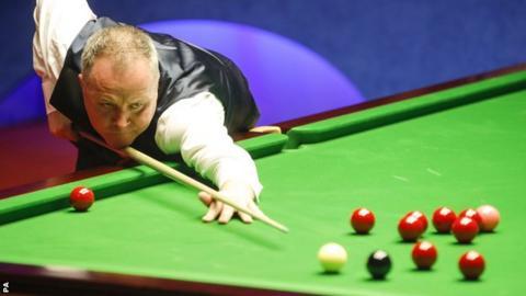 John Higgins plays a shot