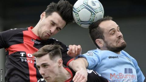Crues midfielder Declan Caddell and Ballymena's Tony Kane contest a high ball