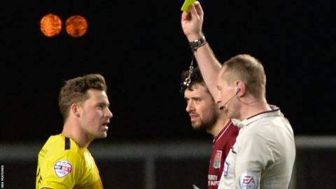 Oxford United striker Chris Maguire booked by referee Keith Hill