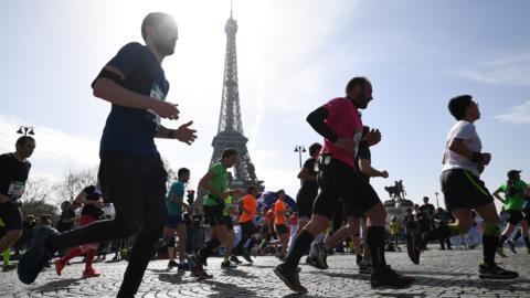 Paris Marathon runners pass the Eiffel Tower