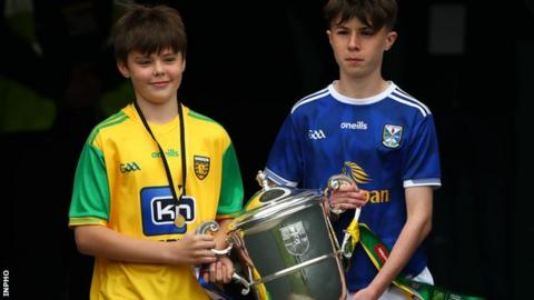 Two young Donegal and Cavan fans carry the Anglo Celt Cup out at Clones ahead of the 2019 Ulster SFC final