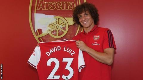 David Luiz holds an Arsenal shirt