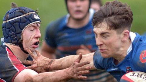Portadown's Daniel Smith attempts to fend off the challenge of Wellington College opponent Callum Stewart