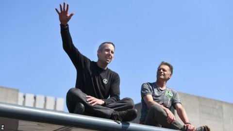 Etienne Stott and Chris Packham make a speech while sitting on top of a bus stop