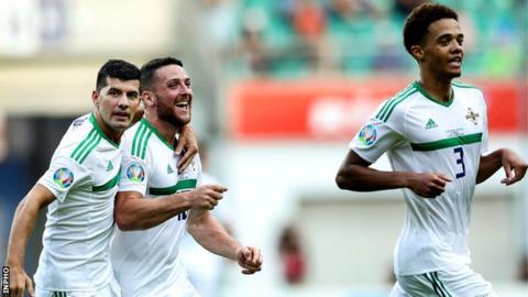 Conor Washington celebrates with Jordan Jones and Jamal Lewis after scoring in Northern Ireland's qualifier win in Estonia in June