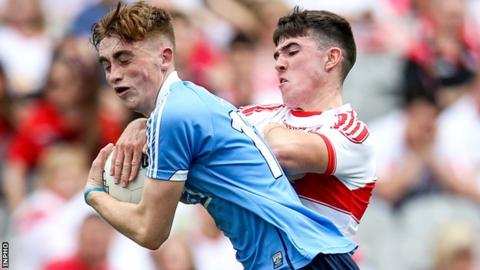 Dublin minor David Lace attempts to shield the ball from Derry's Oran McGill