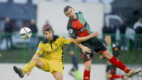 Cliftonville's David McDaid and Glentoran's Jay Magee in action during the Premiership encounter at the Oval