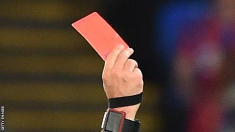 A referee showing a red card