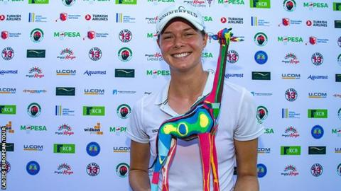 Esther Henseleit smiles holding a giraffe-shaped trophy after winning the Magical Kenya Ladies Open