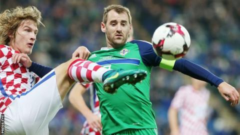 Tin Jedjav challenges Niall McGinn who captained Northern Ireland on the occasion of his 50th cap