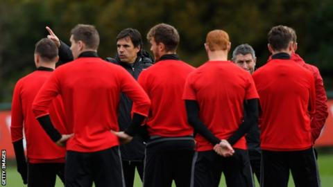 Chris Coleman talks to his players during training