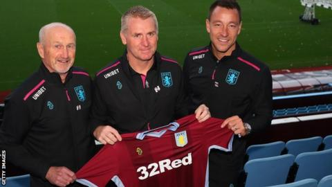 Dean Smith (centre), with assistant coaches John Terry (right) and Richard O'Kelly (left)