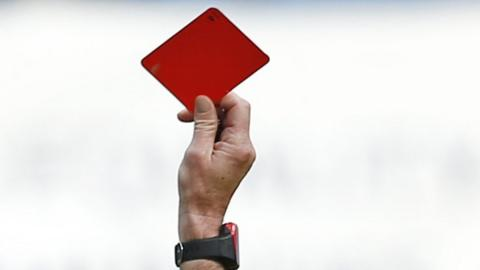 A football referee brandishes a red card