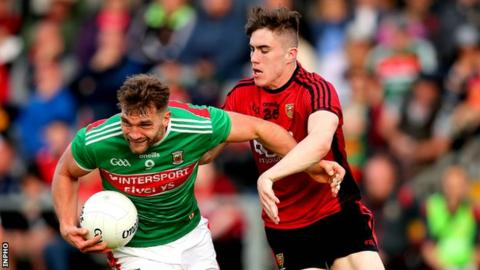 Aidan O'Shea of Mayo attempts to shrug off the challenge of Owen McCabe