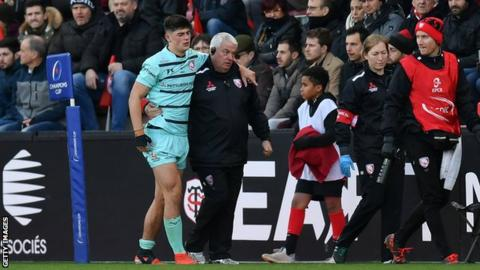 Louis Rees-Zammit is helped from the field