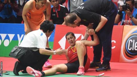 Carolina Marin sits on court in pain