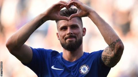 Chelsea forward Olivier Giroud signals a heart shape towards the fans