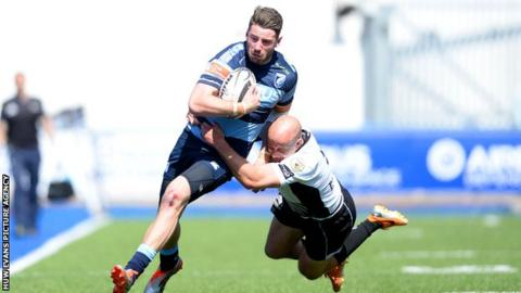 Alex Cuthbert of Cardiff Blues is tackled by Brendon Leonard of Zebre