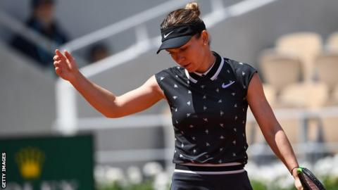 Halep holds up her hand and looks down in disappointment