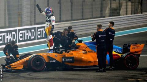 Fernando Alonso waves to the crowd while standing on his McLaren car after the end of his final Grand Prix before retirement in Abu Dhabi
