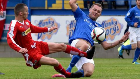 Cliftonville winger Martin Donnelly slides in to challenge Ciaran Caldwell in the Mournview Park clash against Glenavon