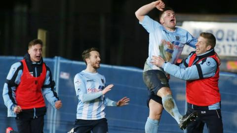 David Cushley leaps high in the air after his deflected strike puts Ballymena 2-1 ahead