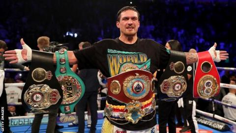 Oleksandr Usyk celebrates with all four world cruiserweight title belts after beating Tony Bellew